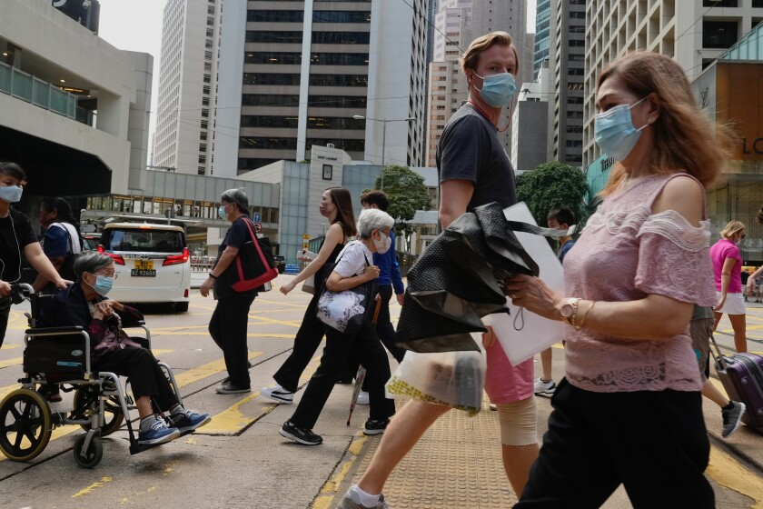 People wearing face masks to prevent the spread of coronavirus walk on a downtown street in Hong Kong, Tuesday, Aug. 17, 2021. Hong Kong will tighten entry restrictions for travelers arriving from the United States and 14 other countries from Friday, increasing the quarantine period to 21 days. (AP Photo/Vincent Yu)