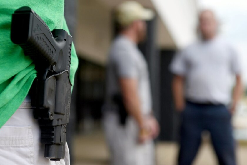 In this photo taken Monday, July 20, 2015, a man who would only give his name as J.R., from Norfolk, Va., stands with his sidearm as dozens of people, some armed with weapons and some carrying water, to the front door of the Armed Forces Career Center in Huntsville, Ala. Armed civilians patrolled t