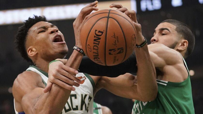 Milwaukee Bucks' Giannis Antetokounmpo is fouled by Boston Celtics' Jayson Tatum during the first ha