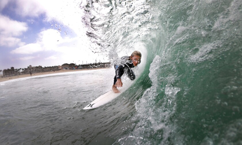 Luke Guinaldo, 13, of Huntington Beach, gets a tube ride after the blessing of the surfers during the first-ever California Surfing Day celebration at the Huntington Beach pier.