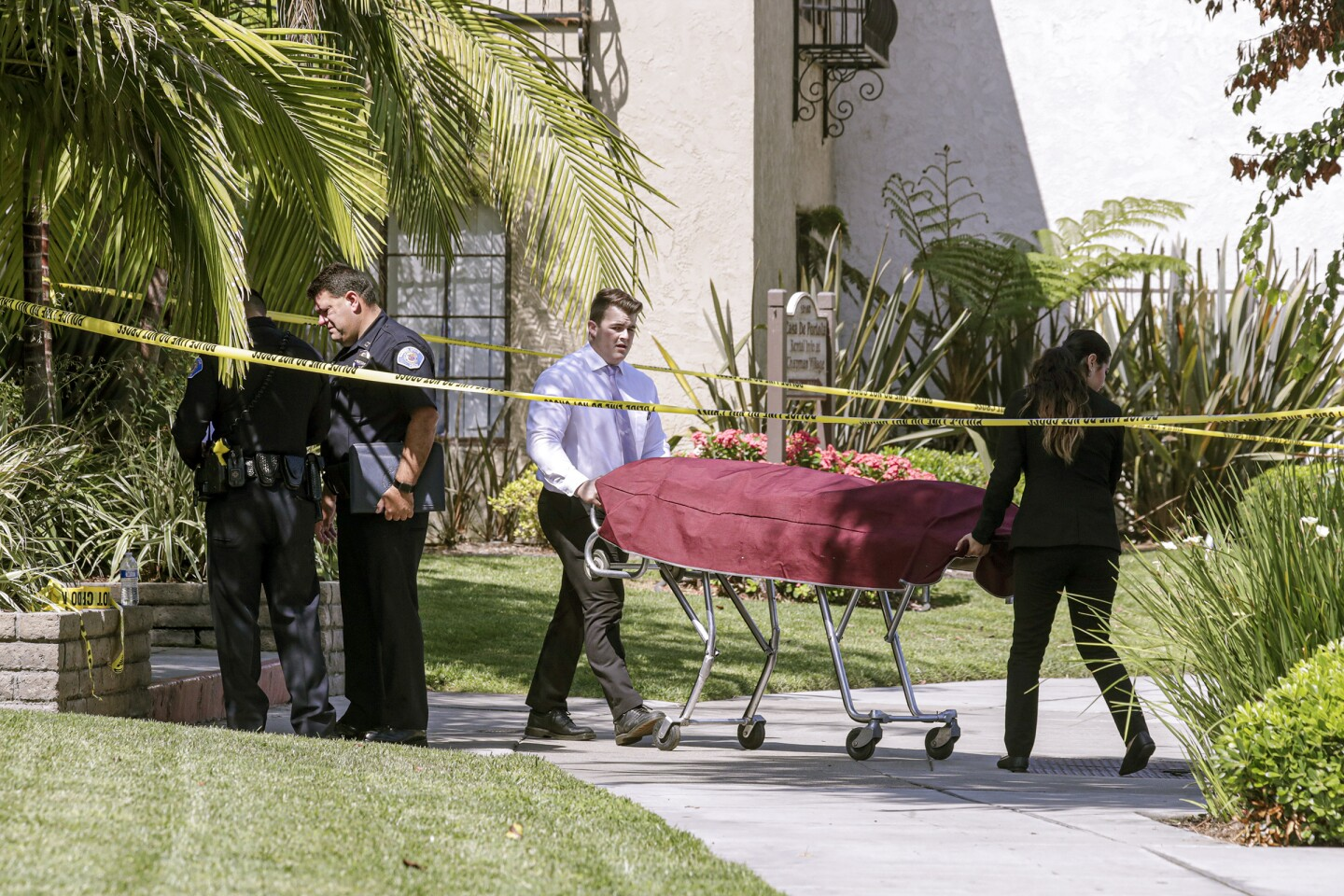 GARDEN GROVE, CA - AUGUST 07, 2019 — Coroners removing the one of the two shooting victims from Casa De Portola apartment complex on 12162 Jentges Ave. Thursday August 08, 2017 morning in Garden Grove. A man stabbed to death two people yesterday before getting on crime spree and killing two more in Orange County. (Irfan Khan/Los Angeles Times)