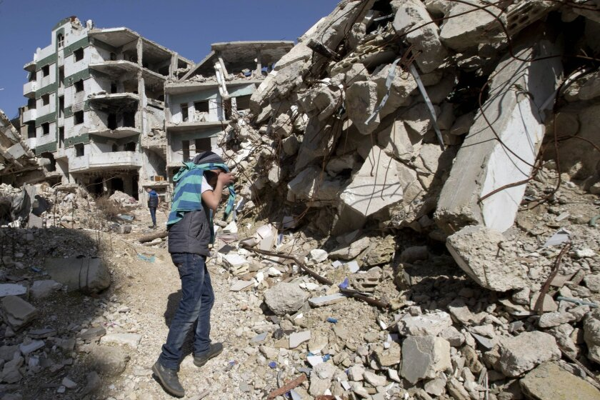 """A Syrian covers his face as he walks with a friend between destroyed buildings in the old city of Homs, Syria, Friday, Feb. 26, 2016. The U.N. Security Council is expected to vote Friday afternoon on a draft resolution endorsing the """"cessation of hostilities"""" in Syria that is set to start at midnight local time. The draft, obtained by The Associated Press, also urges the U.N. secretary-general to resume Syria peace talks """"as soon as possible."""" (AP Photo/Hassan Ammar)"""