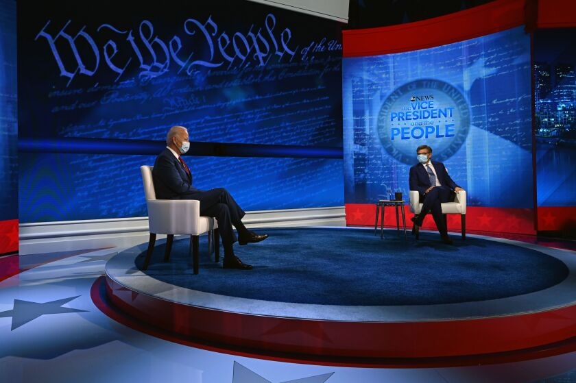 Joe Biden sits across a stage from the moderator in front of a wall with graphics of the Constitution