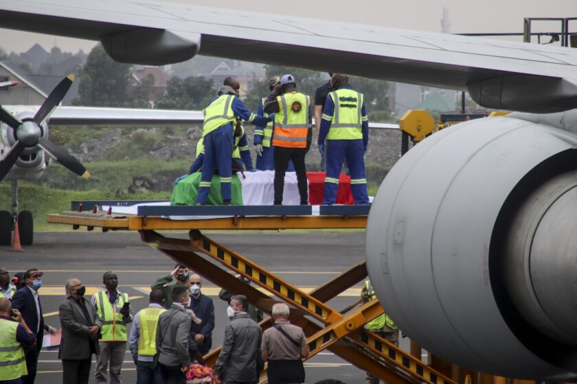 The coffins of Italian ambassador to Congo Luca Attanasio and Carabinieri officer Vittorio Iacovacci, draped with the Italian flag, are loaded onto an airplane for repatriation to Italy, at the airport in Goma, North Kivu province, Congo Tuesday, Feb. 23, 2021. An Italian Carabinieri unit is expected in Congo Tuesday to investigate the killings of the Italian ambassador to Congo, an Italian Carabinieri police officer and their driver in the country's east. (AP Photo/Justin Kabumba)