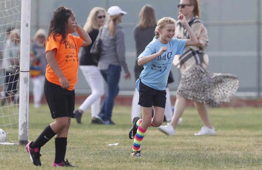 Costa Mesa St. Joachim Catholic School's Madie Willard, right, cheers after scoring her team'sz firs