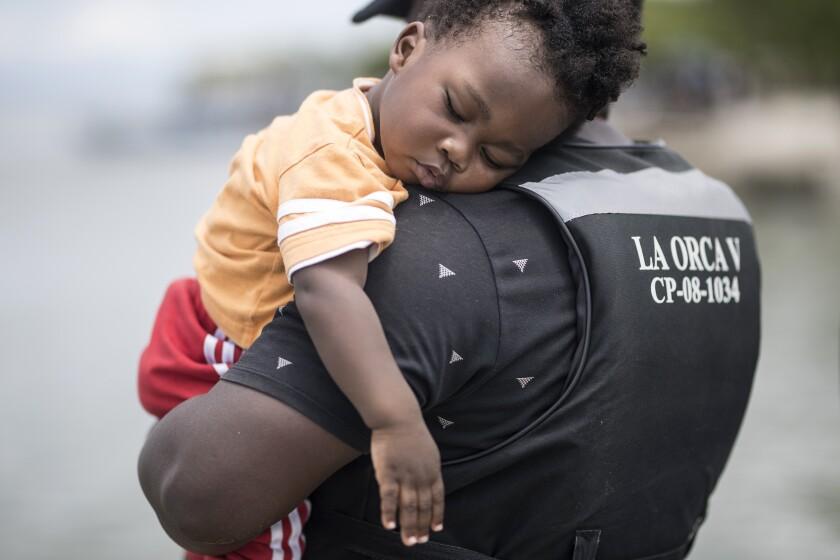 Un migrante haitiano sostiene a su hijo antes de abordar un bote hacia Capurgana cerca de la frontera con Panamá, en Necoclí, Colombia, el miércoles 28 de julio de 2021. Miles de migrantes se han estado reuniendo en Necoclí mientras avanzan hacia el norte hacia Panamá en su camino hacia la frontera con Estados Unidos. (AP Foto/Ivan Valencia)
