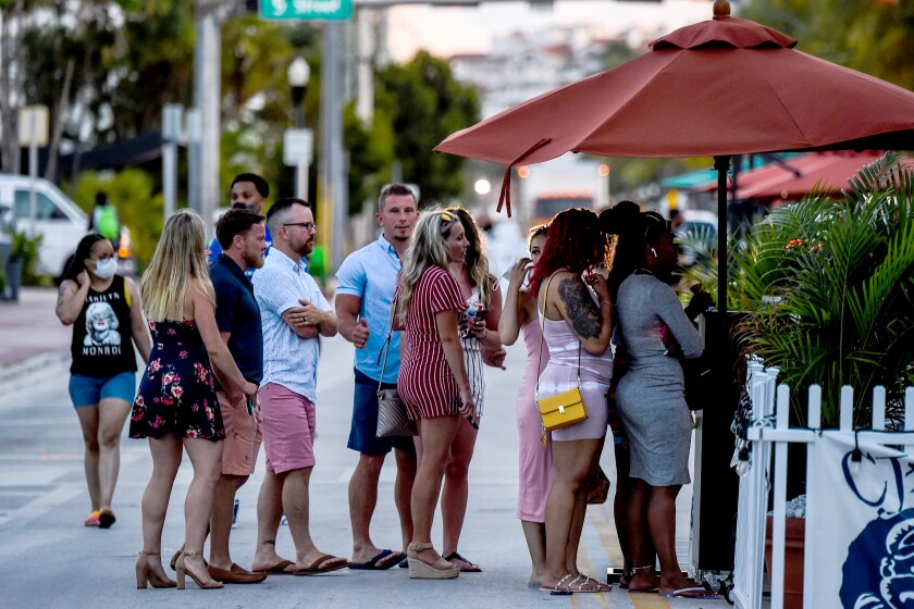People stand in queue to enter a restaurant on Ocean Drive in Miami Beach, Florida on June 26, 2020. - They are itching for a good time after months of lockdown, and may the coronavirus be damned: young adults in Florida are fueling a dangerous rise in COVID-19 infections. Feeling immortal, these fun-crazed people are finding ways to gather and party even though many bars and nightclubs remain closed as the Sunshine State reopened its economy this month. (Photo by CHANDAN KHANNA / AFP) (Photo by CHANDAN KHANNA/AFP via Getty Images)
