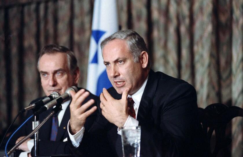 Benjamin Netanyahu, seated, gestures as he speaks into microphones.