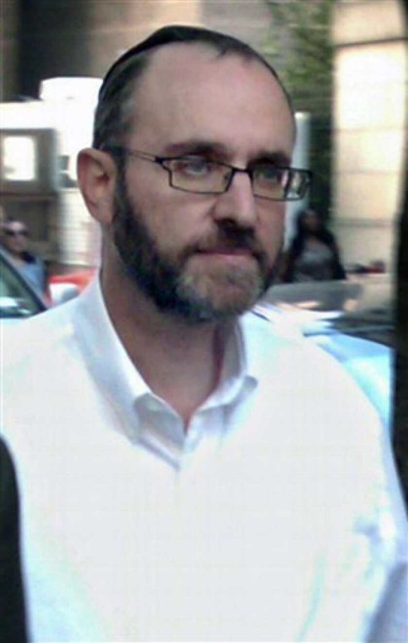 """FILE- In this Aug. 24, 2011 file photo, Menachem Youlus leaves federal court in New York after appearing on mail and wire fraud charges. Youlus, a Jewish charity co-founder who claimed he traveled the world as a """"Jewish Indiana Jones"""" to rescue Torahs, has pleaded guilty to fraud charges on Thursday, Feb. 2, 2012 in New York. (AP Photo/Larry Neumeister, File)"""