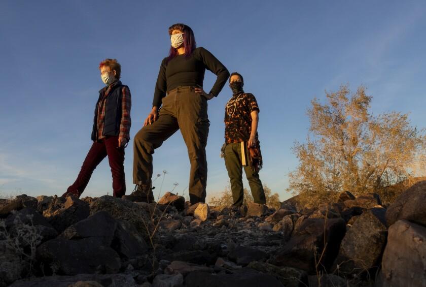 Ellen Mackey, Gina Chavez and Lee King pose for a portrait standing on rocks in a desert landscape