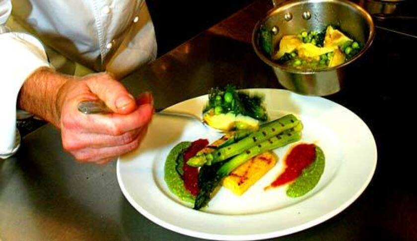 Chef Joe Miller of Joe's restaurant in Venice puts together grilled asparagus with polenta, a dish that works well with fava beans and fresh English peas.