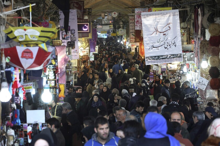 Iranians shop at Tehran's old main bazaar on Monday. As the West temporarily eases some economic sanctions against the country in exchange for restraints on nuclear development, the two sides are putting a different spin on how the ease-up will affect Iran's economy.