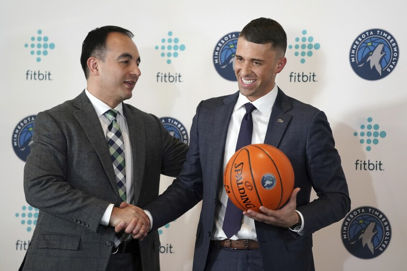 FILE - In this May 21, 2019 file photo Minnesota Timberwolves President of Basketball Operations Gersson Rosas, left, shakes hands with Ryan Saunders, after a news conference in Minneapolis. The season is officially, or mercifully, over for the Minnesota Timberwolves now that the NBA has decided to restart the virus-halted schedule with 22 teams. There was too much disruption to properly assess the job that coach Ryan Saunders did, or the viability of the roster they've settled on for now, but what was clear in 2019-20 was that first-year president Gersson Rosas was capable and willing of making major changes. (Anthony Souffle/Star Tribune via AP)