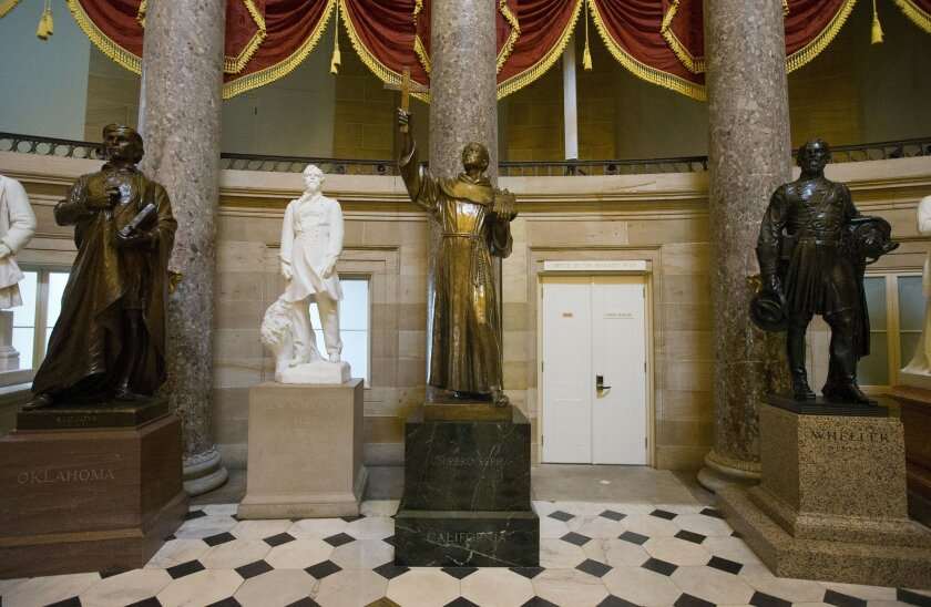 The statue of missionary Junipero Serra, center, is seen in Statuary Hall, also known as the Old Hall of the House, on Capitol Hill in Washington, Thursday, July 2, 2015. California lawmakers are shelving a plan to replace the statue with astronaut Sally Ride, bowing to pressure to drop the idea until after Pope Francis's September visit to the U.S., when he plans to make the 18th century missionary a saint. (AP Photo/Pablo Martinez Monsivais)