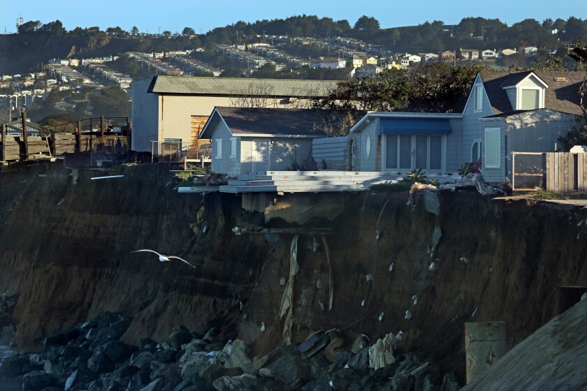 Homes dangle on the edge of a seaside cliff.
