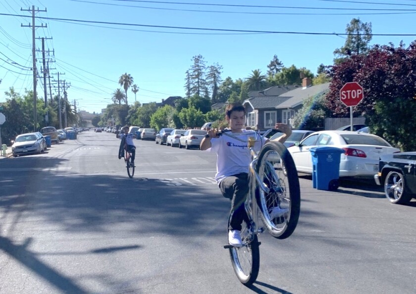 "Javier Melendes, 15 (front) and Jesse Rivera, 13 ride their bikes down one of Redwood City's ""Safe Streets."""