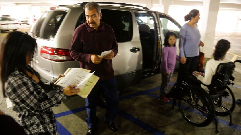 An undercover officer with the Department of Motor Vehicles issues a citation to a family parking in