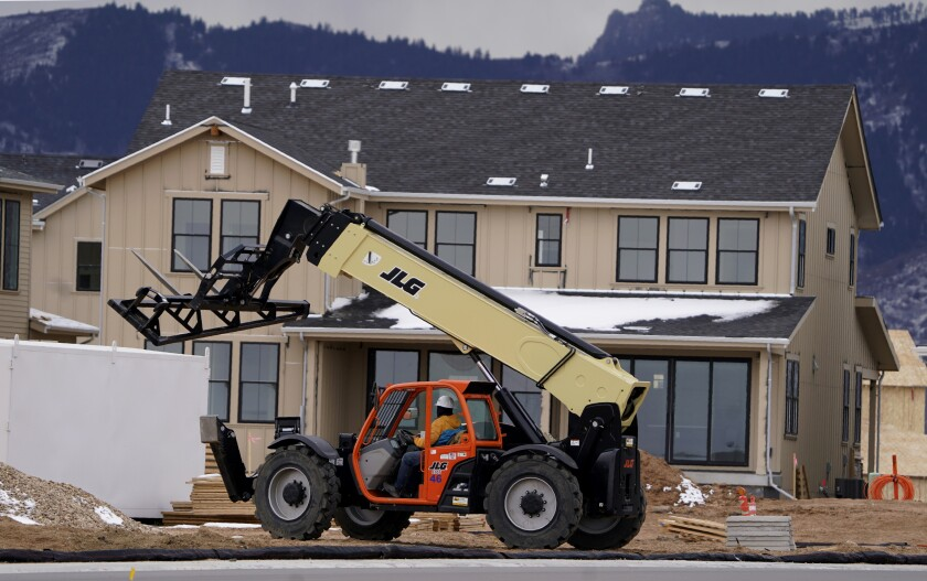 FILE - In this Dec. 1, 2020 file photo, workers toil on new homes under construction in a development near Chatfield State Park in Littleton, Colo. Spending on U.S. construction projects increased 0.9% in November as strength in home building offset weakness in other parts of the construction industry. The Commerce Department said that the November gain followed a bigger 1.6% rise in October and left construction spending up 4.4% through the first 11 months of 2020 compared to the same period in 2019. (AP Photo/David Zalubowski, File)