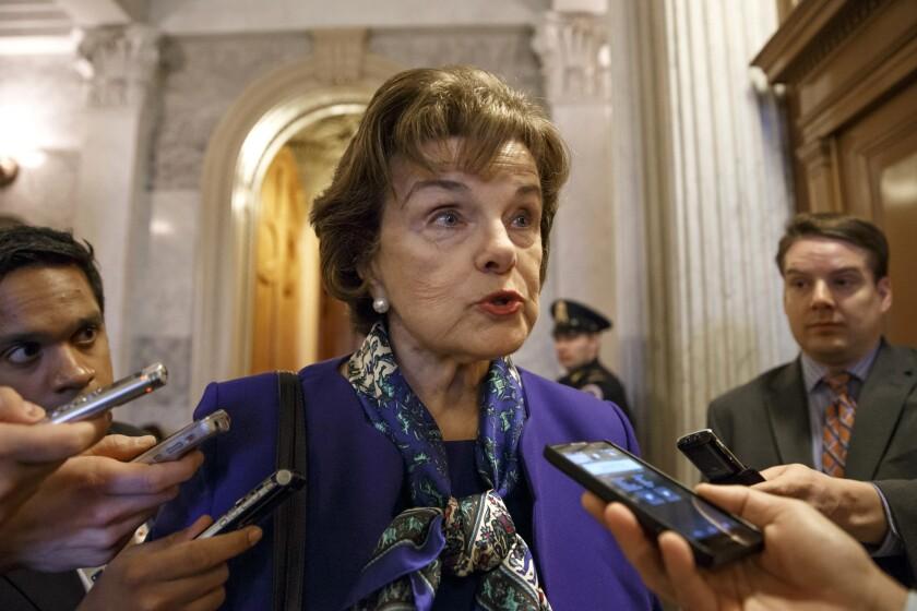 Sen. Dianne Feinstein talks to reporters as she leaves the Senate chamber.