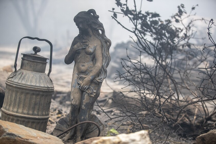 A statue singed by flames sits amid a home destroyed in the Bear fire on Thursday in Feather Falls, a town in Butte County.