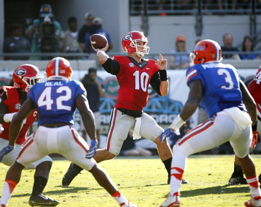 Georgia quarterback Faton Bauta (10) throws a pass as he is pressured by Florida defensive back Keanu Neal (42) and linebacker Antonio Morrison (3) during the first half of an NCAA college football game  Saturday, Oct. 31, 2015, in Jacksonville, Fla. (AP Photo/Stephen B. Morton)