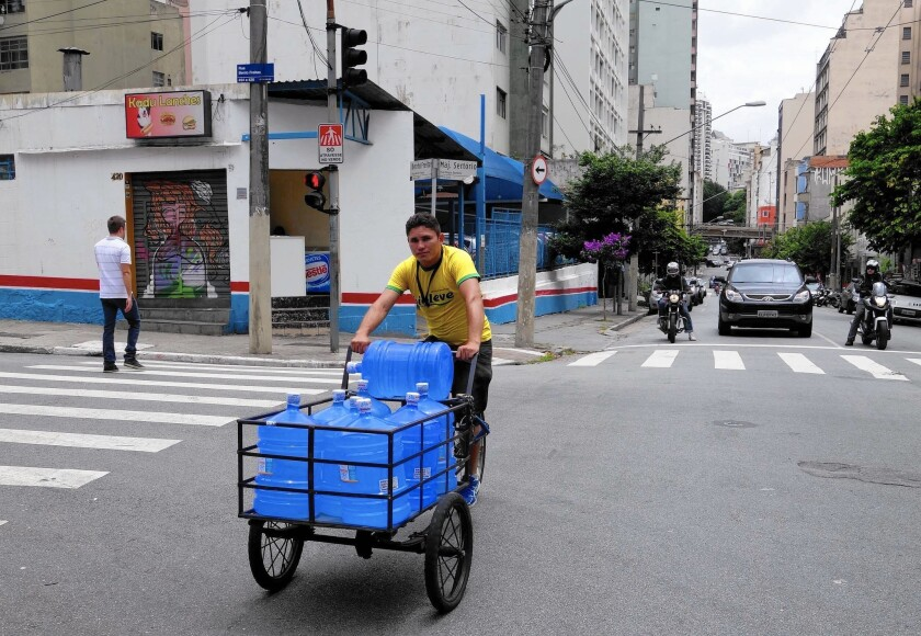 Joao Paulo Bezerra is among the workers risking life and limb to deliver mineral water to restaurants, offices and apartment buildings in Sao Paulo, Brazil.