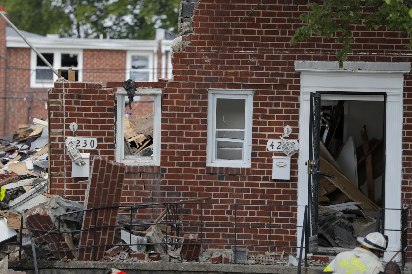 A firefighter walks near the debris in the aftermath of an explosion in Baltimore on Monday, Aug. 10, 2020. Baltimore firefighters say an explosion has leveled several homes in the city. (AP Photo/Julio Cortez)