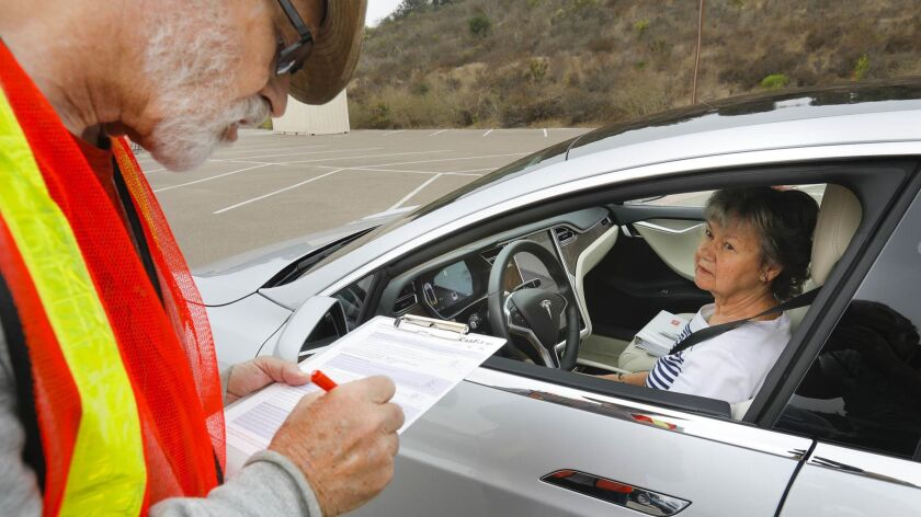 CARLSBAD CA 9/26/2018: Gary Neff, left, AARP District Coordinator goes over the CarFit safety check