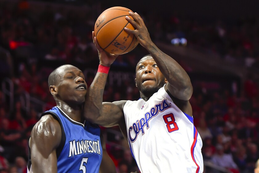 Former Clippers guard Nate Robinson drives past Timberwolves center Gorgui Dieng on March 9, 2015.