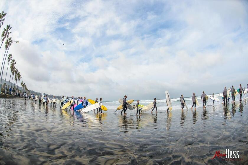Surfers enter the water for the 2016 One Wave Challenge, which was held at the La Jolla Shores beach.