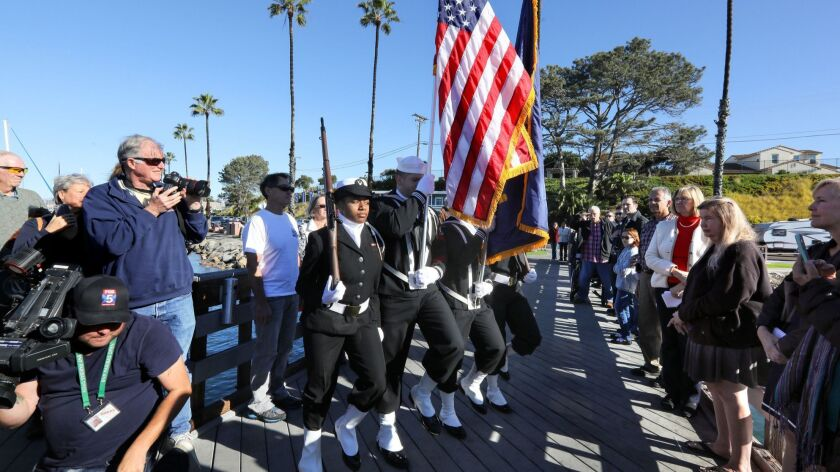A Navy Color Guard begins this morning's Pearl Harbor Memorial event on the small fishing pier at the Oceanside Harbor.