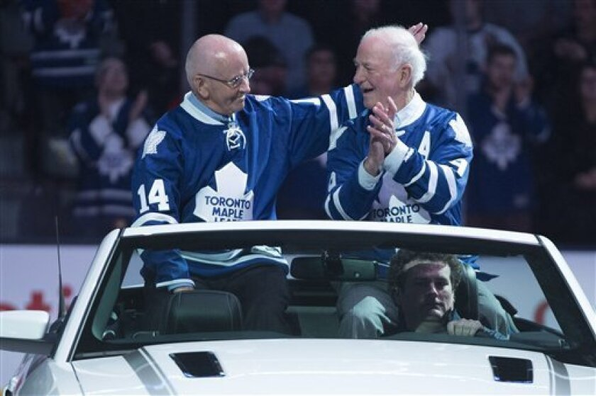 Former Toronto Maple Leafs Dave Keon, left, and Dick Duff, who were on Toronto's 1963 Stanley Cup-winning team, ride in a car on the ice before an NHL hockey game between the Maple Leafs and the Ottawa Senators in Toronto on Saturday, Feb. 16, 2013. (AP Photo/The Canadian Press, Chris Young)