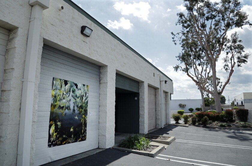 """Chris Trueman's """"DPW,"""" acrylic and acrylic spray paint on yupo, is displayed on a roll-up door in an Upland industrial park."""