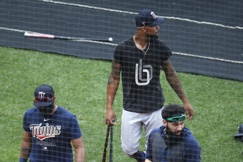Minnesota Twins' Byron Buxton, center, Marwin Gonzalez, right, and another player head to the batting cage during baseball training Wednesday, July 8, 2020, in Minneapolis. Count Buxton among the players who probably benefited from baseball's virus-induced delay. The oft-injured Twins center fielder was coming off major shoulder surgery. After a late arrival due to the birth of his second child, Buxton is in camp at full speed. (AP Photo/Jim Mone)