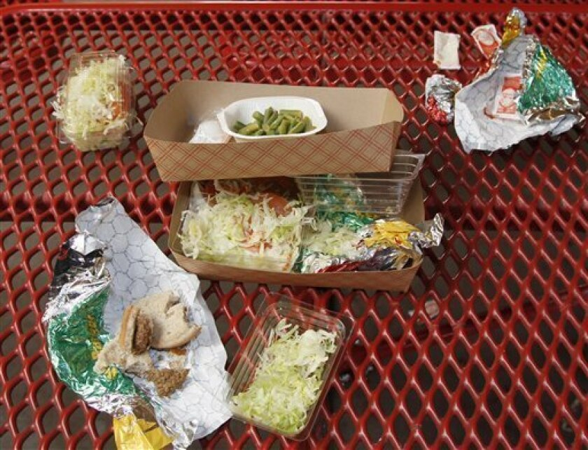 FILE - This Jan. 17, 2012, file photo shows vegetables left over by students on their cafeteria trays at the Roosevelt High School in Los Angeles. Americans blame too much screen time and cheap fast-food for fueling the nation's obesity epidemic, but a poll finds that they're split on how the government should help. A third of people say the government should be deeply involved in finding ways to curb obesity. A similar proportion want the government to play little or no role, and the rest are in the middle. (AP Photo/Damian Dovarganes, File)