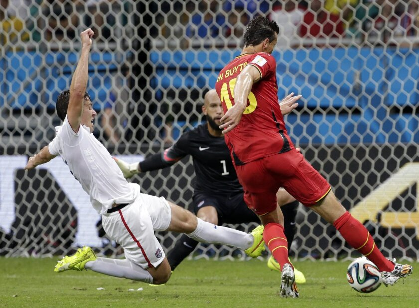 Belgium's Daniel Van Buyten, right, shoots as United States' Matt Besler, left, tries to block during the World Cup round of 16 soccer match between Belgium and the USA at the Arena Fonte Nova in Salvador, Brazil, Tuesday, July 1, 2014. (AP Photo/Felipe Dana)