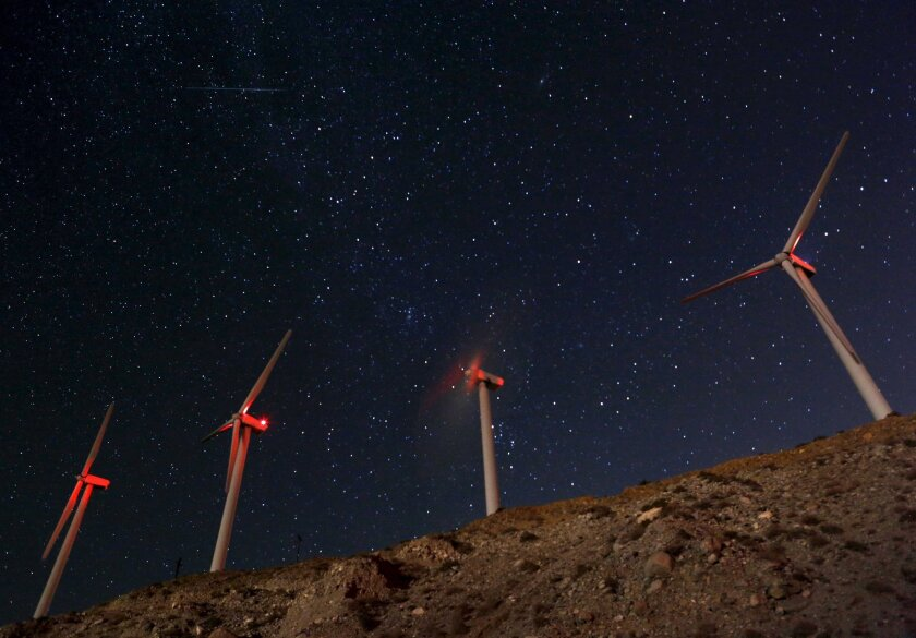 A meteor speeds past windmills at the San Gregornio Pass Wind Farm near Whitewater, CA.