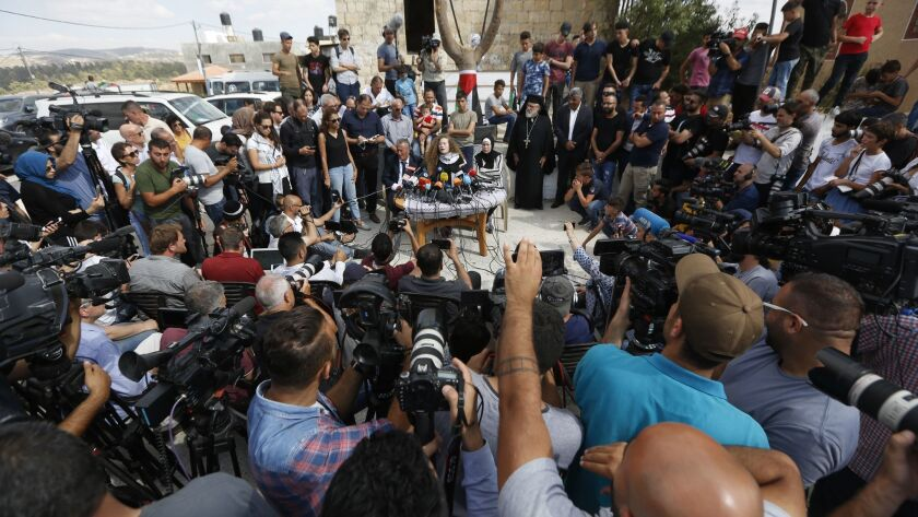 Ahed Tamimi speaks sitting between her father Bassam and mother Nariman during a press conference on