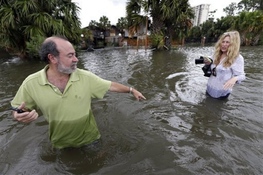 Kenny Melkin, left, helps his wife Becky navigate through floodwaters from Hurricane Isaac as they make their way to see their flooded home in the West End Park neighborhood along Lake Pontchartrain, Friday, Aug. 31, 2012 in New Orleans. Isaac is now a tropical depression and the center was on trac