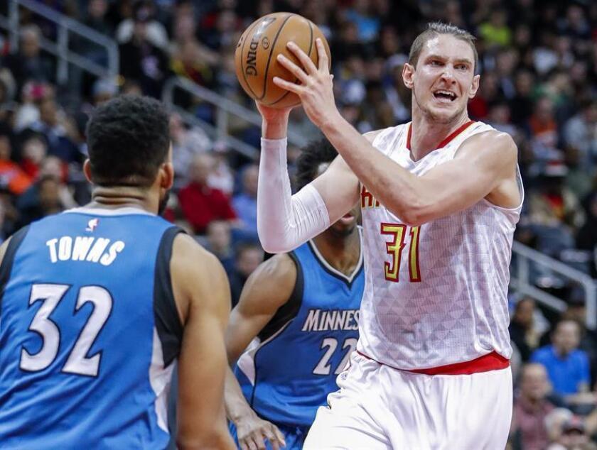 Mike Muscala (d), de Atlanta Hawks, busca pasar el balón frente a Karl-Anthony Towns (i), de Minnesota Timberwolves, durante un partido de la NBA en Philips Arena en Atlanta (EE.UU.). EFE