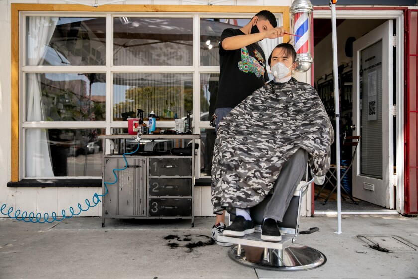 Barber Ivan Plascencia gives a haircut