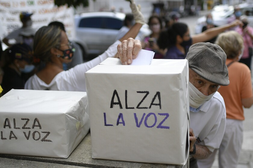 An elderly man votes in a consultation organized by the opposition to reject the government of President Nicolas Maduro in Caracas, Venezuela, Saturday, Dec. 12, 2020. The survey, asking Venezuelans to weigh in via cellphone apps or in-person voting whether they want to see an end to Maduro's rule and new elections, takes place just days after the governing party won congressional elections boycotted by the opposition. (AP Photo/Matias Delacroix)