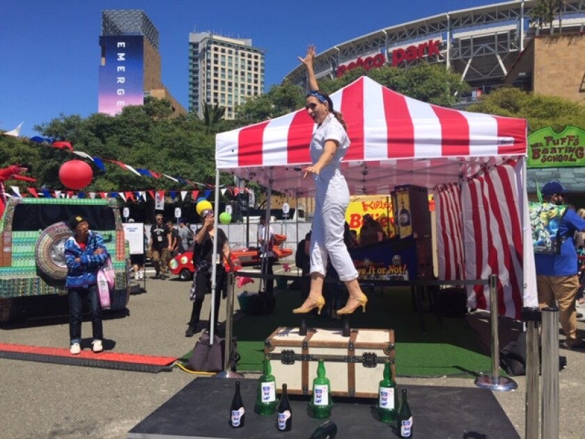 An acrobat from Ripley's Believe it or Not! balances her body weight on the heads of two bottles Friday morning at the Petco Park Interactive Zone