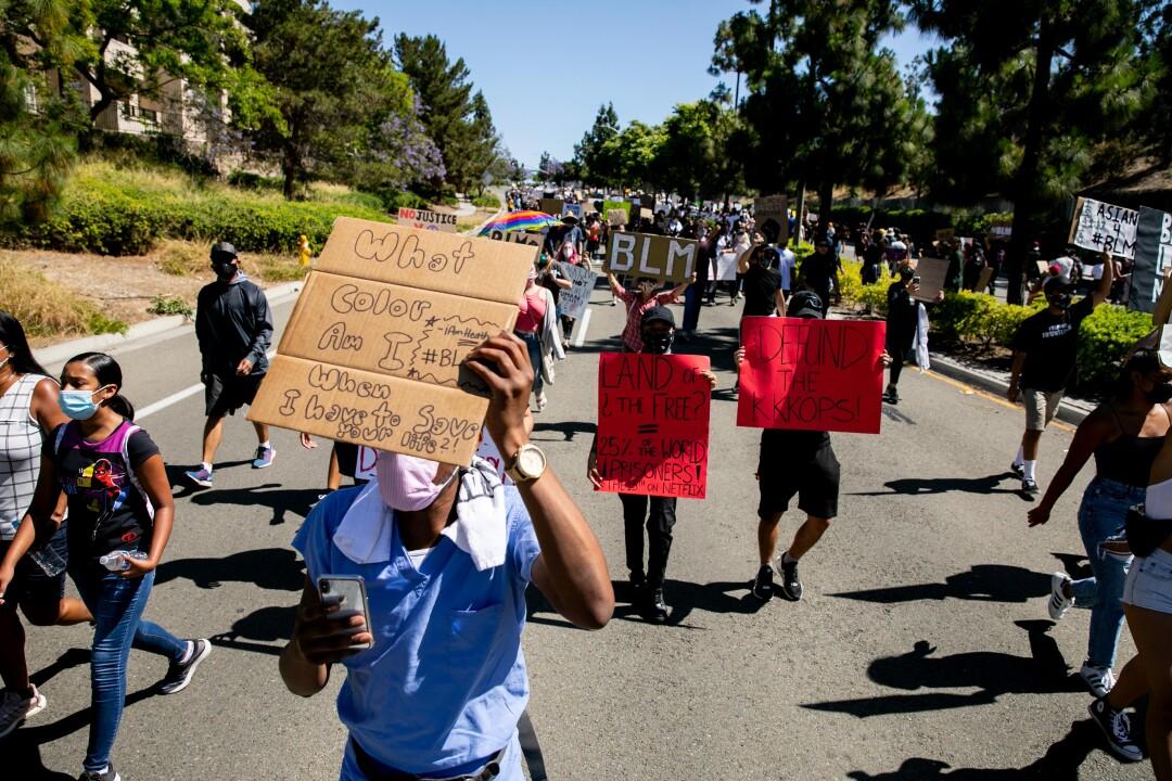 Los manifestantes marchan a lo largo de Eastlake Parkway en demanda de justicia racial.