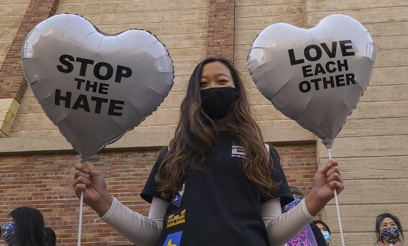 Chinese-Japanese American student Kara Chu, 18, holds a pair of heart balloons