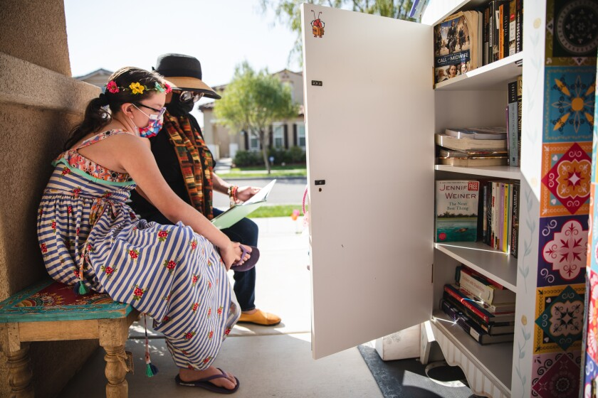Fernanda Padilla and her mother, Katia, read by their Little Library near their Chula Vista home Tuesday.