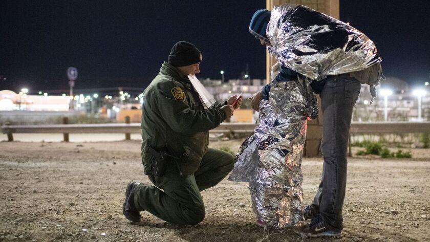 Border Patrol Agent Ramiro Cordero puts arm bands on Mairon Argueta and his daughter Elsi Argueta, 4