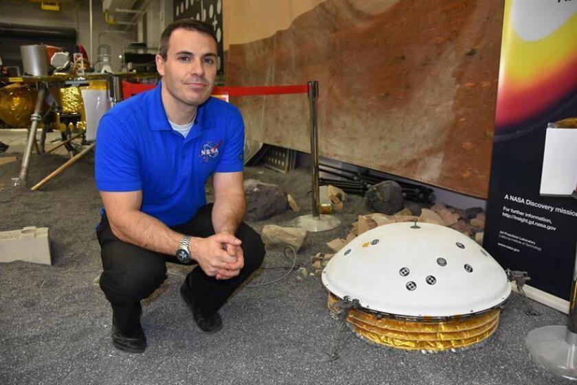 El subdirector de diseño y navegación del módulo estacionario InSight del Laboratorio de Propulsión de la Agencia Nacional Aeroespacial (JPL-NASA), Fernando Abilleira, posa junto a una réplica funcional del InSight en un laboratorio este 26 de noviembre de 2018, en Pasadena, California (EE.UU.). EFE