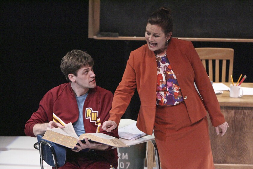 """Miss Edwards (Stephanie Zimbalist) explains the use of a dictionary to her reluctant student (William Reinbold) in Lissa Levin's """"Sex and Education"""" at the Colony Theatre."""