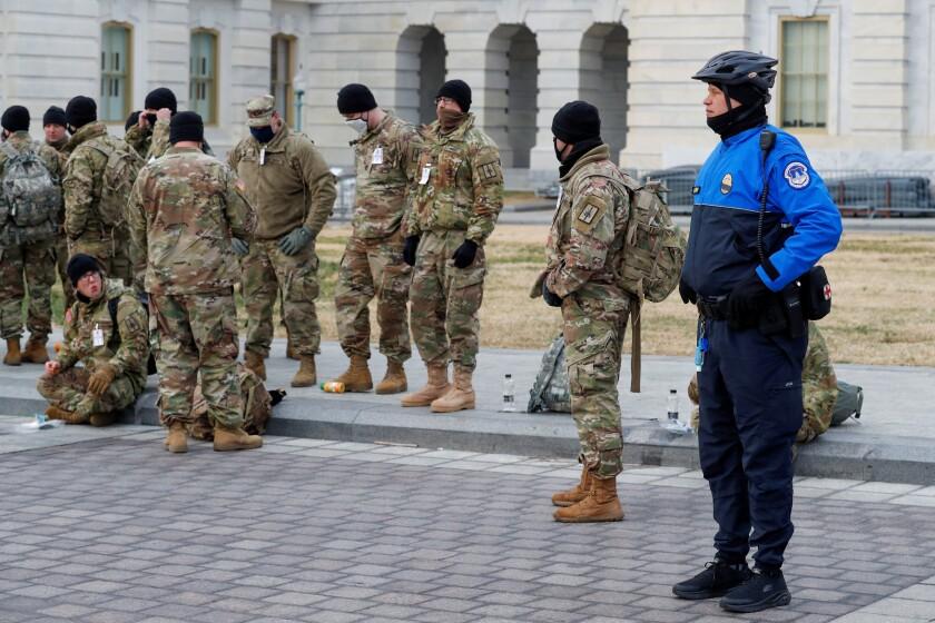 Oficiales de policía del Capitolio  observan cómo miembros de la Guardia Nacional de Nueva York se organizan